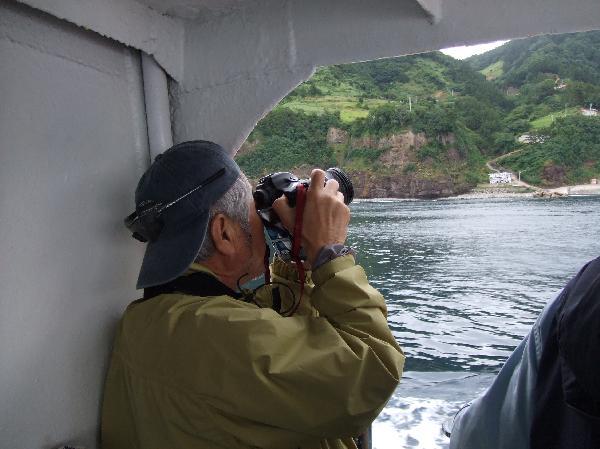地球の島めぐり_韓国_鬱陵島_身体を壁に固定して撮影する筆者